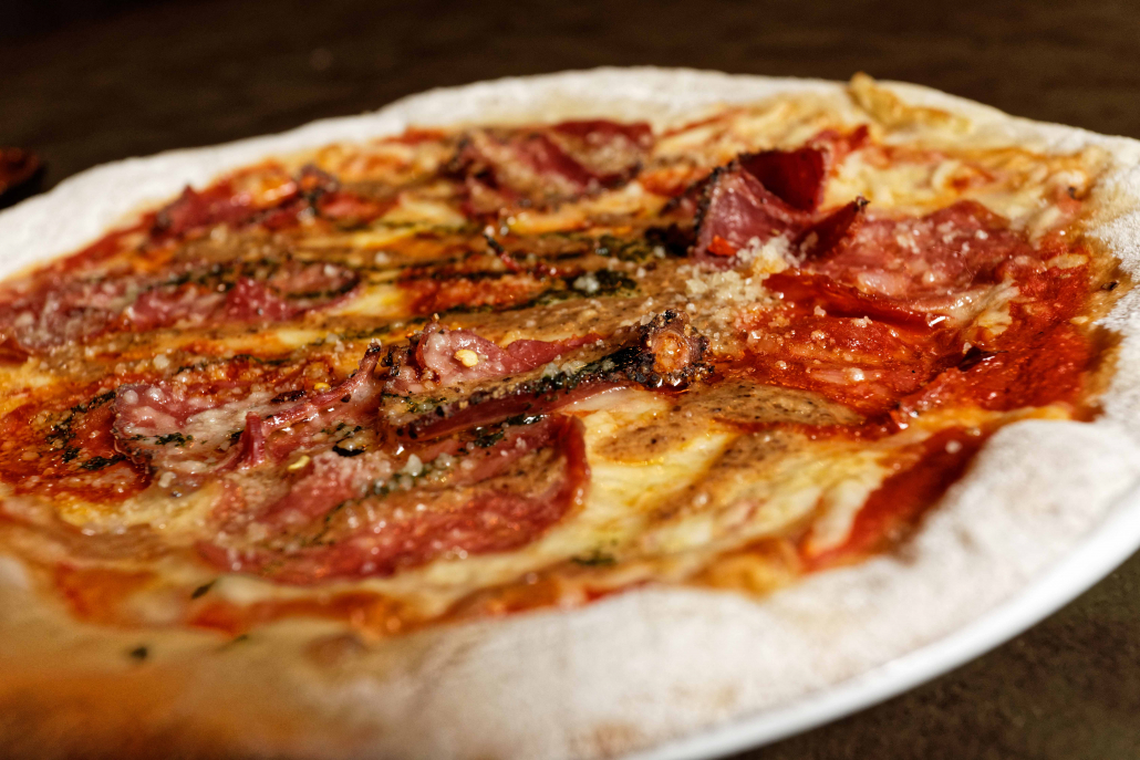 A picture of our wood-fired pizza topped with cheese and meat