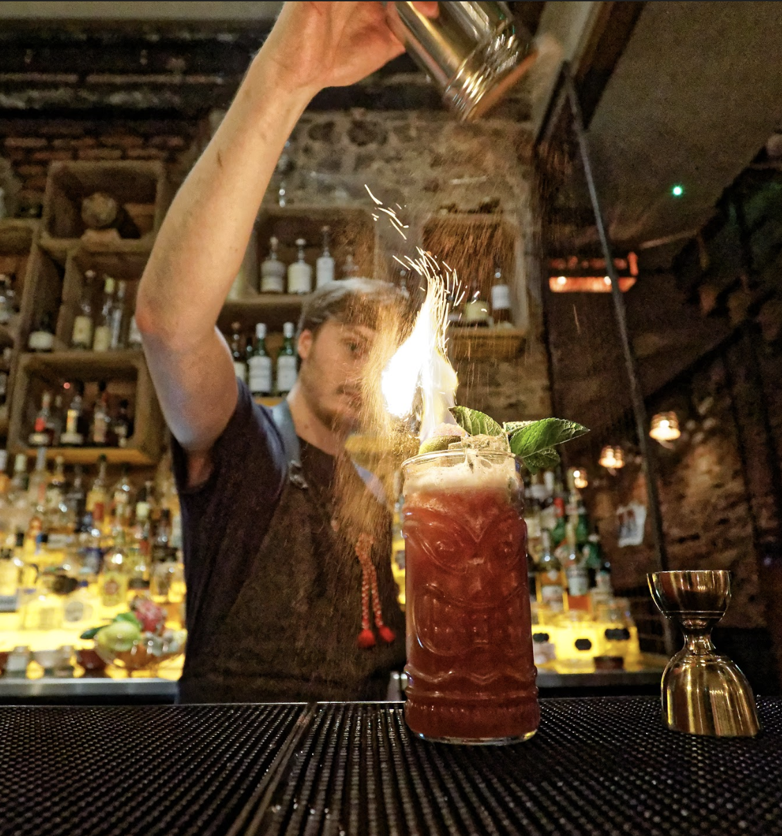A picture of our bartender making cocktails with fire and rum